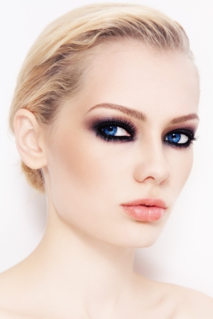 smoky eyes: Close-up portrait of young beautiful woman with smoky eyes, on white wall