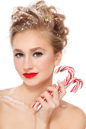 Portrait of young beautiful smiling happy girl with stylish make-up and hairdo, candy canes in hands and snowflakes in her hair photo