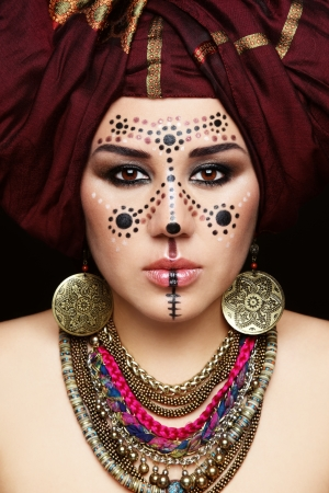 turban: Portrait of young beautiful woman with traditional Berber face paint and turban