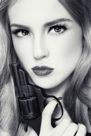 women with guns: Close-up duotone portrait of young beautiful woman with revolver in her hand