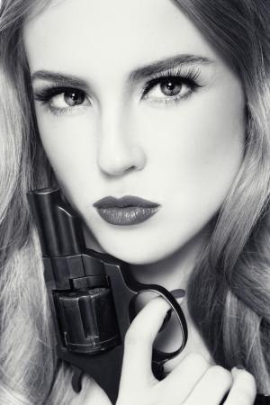 mujer con pistola: Retrato de duotono de hermosa joven con el revólver en la mano Foto de archivo