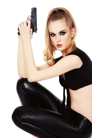 Young beautiful slim sexy blond woman with gun in her hands, on white background photo