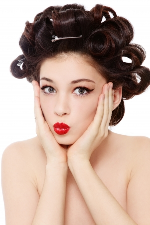 Humorous shot of young pretty girl with hair curles and surprised expression, over white background