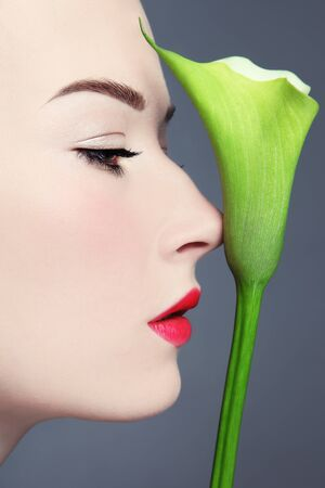 free radicals: Profile portrait of young beautiful woman with fancy green flower
