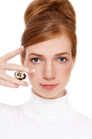 Young red-haired girl with freckles holding quail egg in her hand, on white background photo