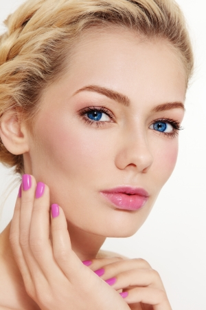 Close-up portrait of young beautiful woman with clear make-up and pink manicure Stock Photo