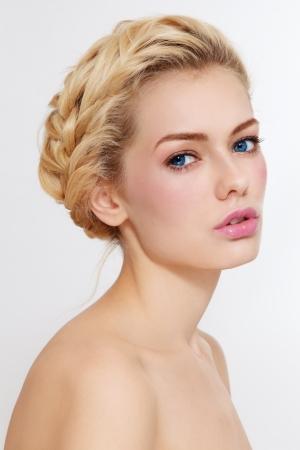 Junge schöne gesunde blonde Mädchen mit Zöpfen und klaren Make-up auf weißem Hintergrund Lizenzfreie Bilder