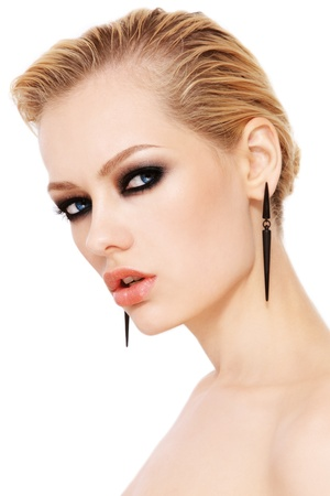 smoky eyes: Portrait of young beautiful woman with smoky eyes and fancy earrings, on white background