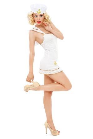 흰색 배경 위에 금발 곱슬 머리와 선원처럼 옷을 입고 세련된 메이크업, 젊은 아름 다운 슬림 섹시한 여자