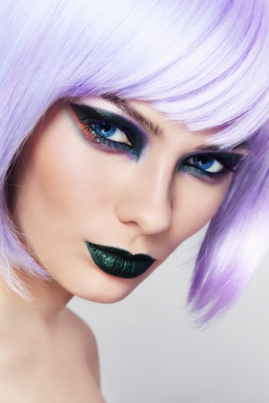 Close-up Portrait der jungen schönen Frau mit bunten Phantasie Make-up und Violett Perücke