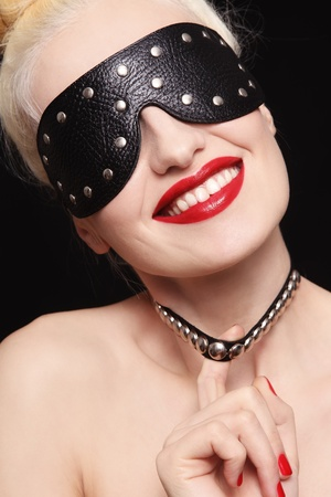 Portrait of young beautiful smiling woman in studded blindfold and collar Stock Photo - 16711466