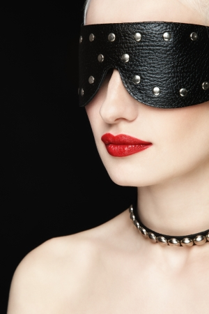 bdsm: Portrait of young beautiful woman in studded blindfold