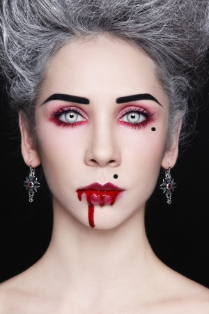 Portrait of young beautiful stylish gothic woman with vintage hairdo and bloody mouth photo