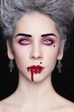 vampira sexy: Retrato de joven y bella mujer con estilo g�tico con el peinado de �poca y la boca ensangrentada