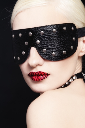 Portrait of young beautiful woman in studded blindfold photo