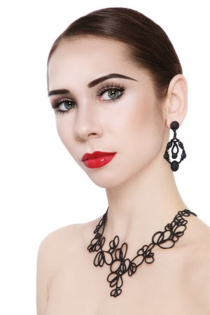 Portrait of young beautiful woman in stylish elegant necklace and earrings, on white background
