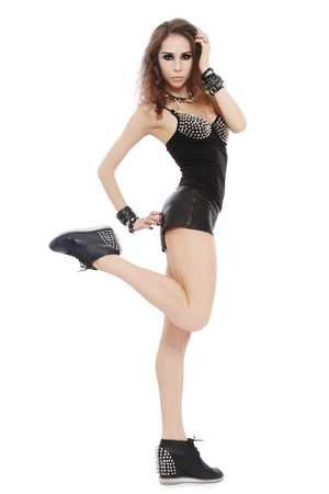 spiked: Young beautiful slim girl in sexy leather shorts and stylish spike boots over white background Stock Photo