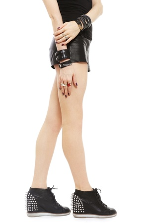 Beautiful legs of fit sexy woman in stylish spike boots and leather shorts, over white background Stock Photo - 17076799