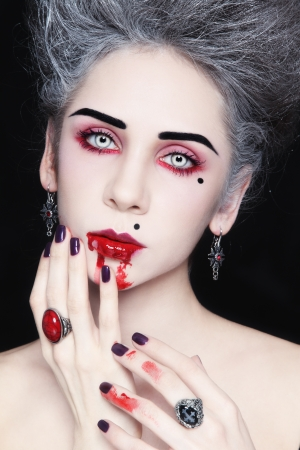 Portrait of young beautiful stylish gothic woman with vintage hairdo and bloody mouth Stock Photo - 17104314
