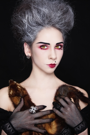goth girl: Portrait of young beautiful woman with vintage hairdo and ferret in her hands