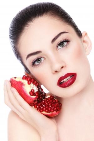 Portrait der jungen schönen Frau mit Granatäpfeln in den Händen, auf weißem Hintergrund