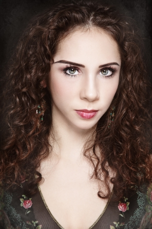 Portrait of young beautiful woman with curly hair and fancy make-up on vintage grainy damaged background Stock Photo - 17478136