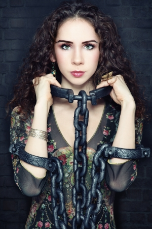 빈티지 거친 손상된 배경 위에 그녀의 목에 무거운 사슬을 가진 젊은 아름 다운 여자, 스톡 콘텐츠