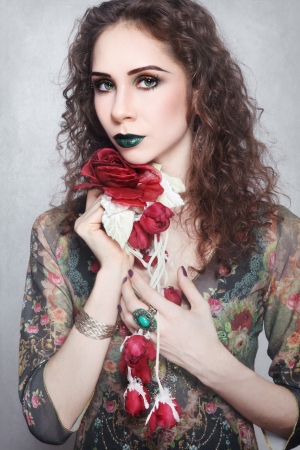Portrait of young beautiful woman with fancy make-up and silk flower in her hands, on vintage grainy damaged background Stock Photo - 17478135