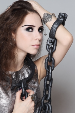 Portrait of young beautiful woman with heavy chain on her neck and arms photo