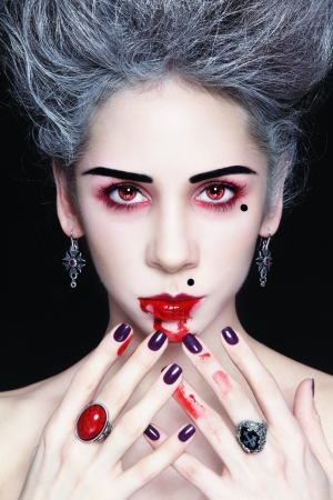 beautiful vampire: Portrait of young beautiful stylish gothic woman with vintage hairdo and bloody mouth Stock Photo