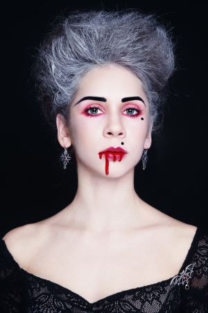 Young beautiful stylish gothic woman with vintage hairdo and bloody mouth photo