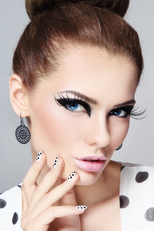 Close-up portrait of young beautiful girl with fancy cat eyes and polka dot manicure