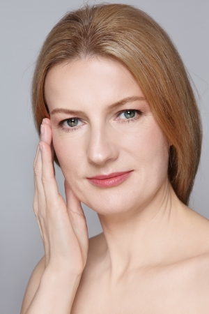 Portrait of attractive mature woman with clean skin touching her face Standard-Bild