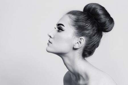 Tiro en blanco y negro de la muchacha hermosa joven con el pelo bollo