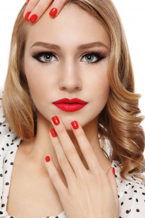 Portrait of young beautiful blonde girl with red lips and manicure photo
