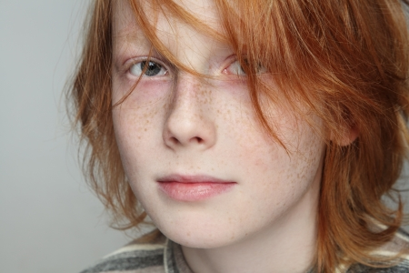 freckled: Close-up portrait of sad and thoughtful freckled teen boy