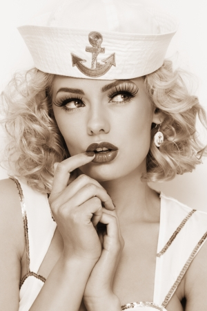 girl doll: Duotone portrait of young beautiful sexy girl with blond curly hair and stylish make-up dressed as sailor Stock Photo