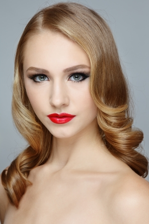 Portrait of young beautiful blond girl with red lipstick and stylish hairdo photo