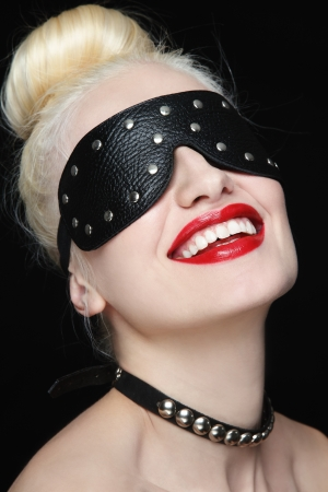 Portrait of young beautiful smiling woman in studded blindfold and collar photo