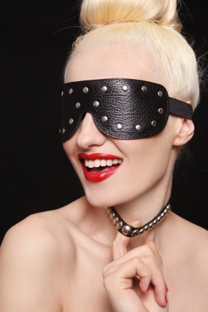 blinder: Portrait of young beautiful smiling woman in studded blindfold and collar Stock Photo