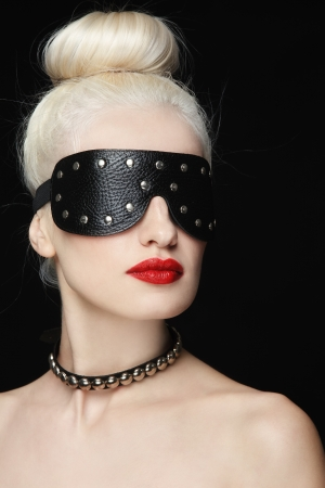 Portrait of young beautiful blond woman in studded blindfold photo