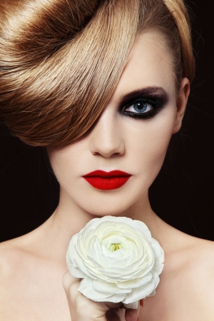 smoky eyes: Young beautiful woman with fancy hairdo and smoky eyes holding white flower in her hand