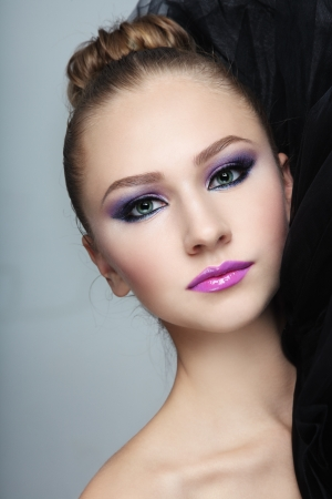 Portrait of young beautiful girl with fancy make-up and hair bun photo