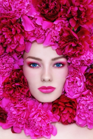 Portrait of young beautiful blue-eyed woman with pink peonies around her face Stock Photo - 19550407