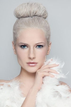 piuma bianca: Ritratto di giovane donna bellissima con i capelli raccolti in polvere d'epoca in bianco e boa di piume