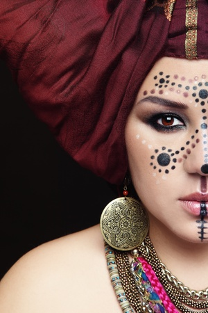 faceart: Close-up portrait of young beautiful woman with traditional Berber face paint and turban