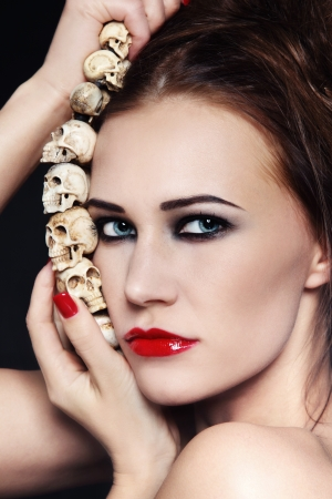 Portrait of young beautiful woman with stylish make-up and skull necklace in her hands photo