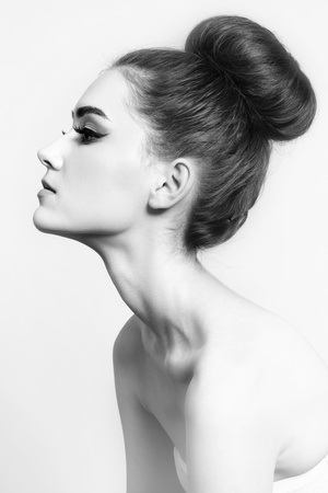60s fashion: Black and white shot of young beautiful girl with hair bun