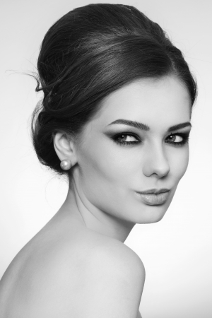 Black and white portrait of young beautiful woman with stylish hair bun photo