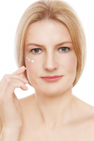 free radicals: Portrait of mature beautiful healthy woman applying cream on her face, over white background